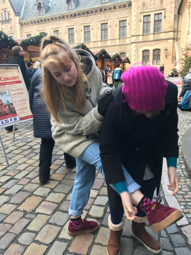 Anya assisting Bianca with tying her shoelaces